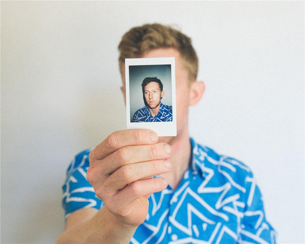 自分の顔写真で顔を隠す男性